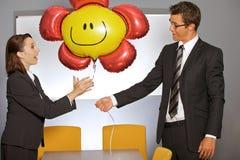 Homme d'affaires donnant le ballon à la femme d'affaires dans le bureau Photographie stock libre de droits