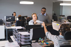 Homme d'affaires donnant le document au collègue travaillant au bureau photographie stock