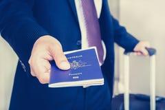 Homme d'affaires donnant le passeport avec la carte d'embarquement à l'intérieur Photo libre de droits