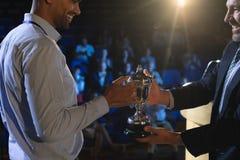Homme d'affaires donnant le trophée à l'exécutif masculin d'affaires sur l'étape dans l'amphithéâtre photographie stock libre de droits