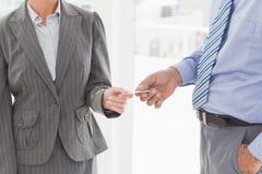 Homme d'affaires donnant sa carte de visite professionnelle de visite à son collègue images libres de droits