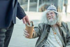 Homme d'affaires donnant un billet d'un dollar au pauvre musicien de rue Images stock