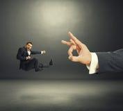 Homme d'affaires donnant un coup de pied, chiquenaude de grande main image libre de droits