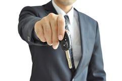 Homme d'affaires donnant une clé de voiture - vente de voiture et concept de location Photographie stock libre de droits