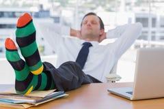 Homme d'affaires dormant avec des pieds sur son bureau image stock