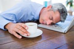 Homme d'affaires dormant sur l'ordinateur portable et la tasse de café émouvante Image stock