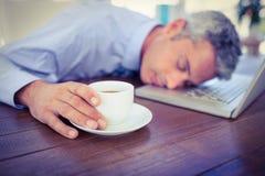 Homme d'affaires dormant sur l'ordinateur portable et la tasse de café émouvante Image libre de droits