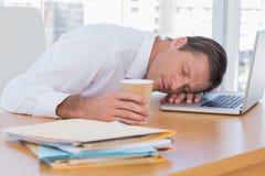 Homme d'affaires dormant sur un ordinateur portable photo stock