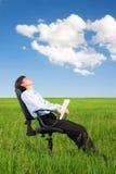 Homme d'affaires détendant sur la prairie sous le ciel bleu Image libre de droits