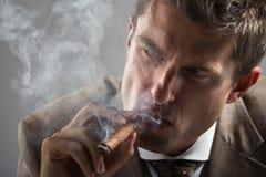 Homme d'affaires dur de regard fixe tout en fumant un cigare cubain Photographie stock libre de droits