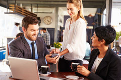 Homme d'affaires effectuant le paiement par carte de crédit dans un café images stock