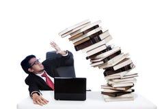 Homme d'affaires effrayé avec la pile des livres Image stock