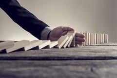 Homme d'affaires empêchant des dominos de s'émietter avec la paume Photographie stock libre de droits