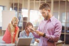 Homme d'affaires employant au téléphone dans le bureau avec travailler de collègues Image libre de droits