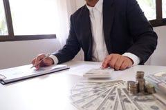 Homme d'affaires employant la calculatrice avec des pièces de monnaie et l'argent au-dessus du bureau photographie stock libre de droits