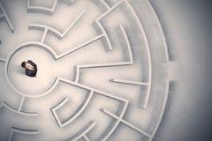 Homme d'affaires emprisonné dans un labyrinthe circulaire image stock