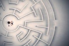 Homme d'affaires emprisonné dans un labyrinthe circulaire images stock