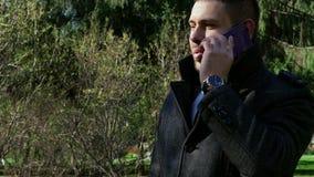 Homme d'affaires en parc de ville parlant au téléphone portable clips vidéos