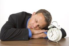 Homme d'affaires en sommeil sur le bureau par une horloge d'alarme Images libres de droits