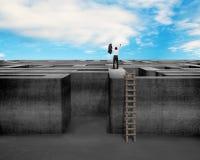 Homme d'affaires encouragé s'élevant sur le mur de labyrinthe avec le ciel Photos libres de droits