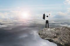 Homme d'affaires encourageant sur la falaise avec le cloudsca naturel de lumière du jour de ciel Photo libre de droits