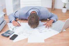 Homme d'affaires enfoncé par la comptabilité photographie stock libre de droits