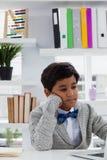 Homme d'affaires ennuyé avec la main sur le menton utilisant l'ordinateur portable photographie stock