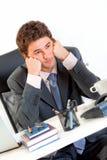Homme d'affaires ennuyé dans la tête de subsistance de bureau sur des mains Photos libres de droits