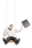 Homme d'affaires enthousiaste balançant sur une oscillation Photographie stock libre de droits
