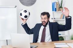 homme d'affaires enthousiaste dans le costume avec du ballon de football regardant l'écran d'ordinateur portable sur le lieu de t photos stock