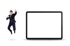 Homme d'affaires enthousiaste sautant avec le panneau d'affichage vide Image stock
