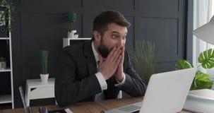 Homme d'affaires enthousiaste travaillant sur l'ordinateur portable banque de vidéos