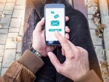 Homme d'affaires envoyant le message électronique par l'intermédiaire du smartphone moderne images libres de droits