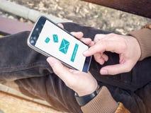 Homme d'affaires envoyant le message électronique par l'intermédiaire du smartphone moderne photographie stock
