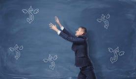 Homme d'affaires essayant d'attraper des symboles dollar avec des ailes dessinées sur le tableau noir bleu Photos libres de droits