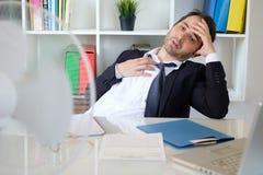 Homme d'affaires essayant de r?g?n?rer au travail dans la chaleur d'?t? image libre de droits