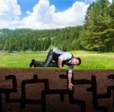 Homme d'affaires essayant de trouver quelque chose dans le sol Image stock