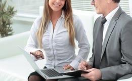 Homme d'affaires et assistant sup?rieurs ? l'aide d'un ordinateur portable se reposant dans le lobby du bureau image libre de droits
