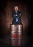 Homme d'affaires et baril mûrs de pétrole brut sur le fond foncé image libre de droits