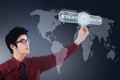 Homme d'affaires et bouton marche asiatiques Photo stock