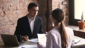 Homme d'affaires et femme d'affaires argumentant au sujet des documents, pointage étant en désaccord aux papiers banque de vidéos