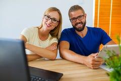 Homme d'affaires et femme d'affaires analysant des diagrammes sur l'ordinateur portable et l'étiquette image stock