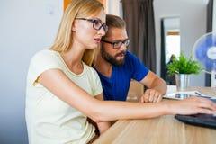 Homme d'affaires et femme d'affaires analysant des diagrammes sur l'ordinateur portable et l'étiquette photographie stock