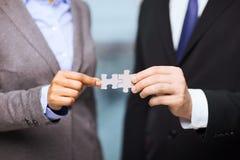 Homme d'affaires et femme d'affaires avec des morceaux de puzzle Photos stock
