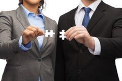 Homme d'affaires et femme d'affaires avec des morceaux de puzzle Photo libre de droits