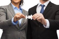 Homme d'affaires et femme d'affaires avec des morceaux de puzzle Photographie stock libre de droits