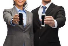 Homme d'affaires et femme d'affaires avec des smartphones Photos stock