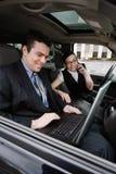 Homme d'affaires et femme d'affaires dans un véhicule Photographie stock libre de droits