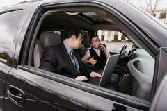 Homme d'affaires et femme d'affaires dans un véhicule Photo stock