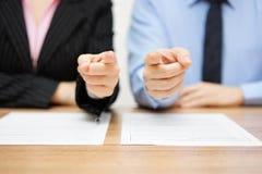 Homme d'affaires et femme d'affaires indiquant avec des doigts vous Staf Photos stock